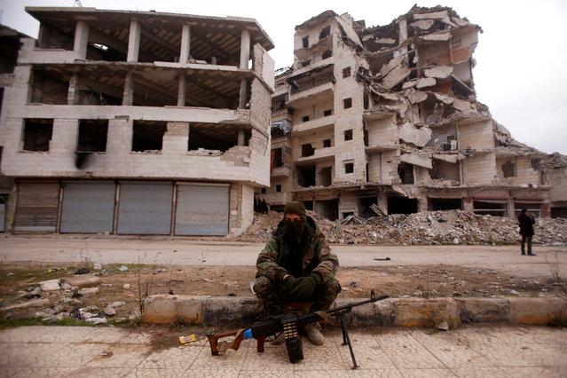 A member of forces loyal to Syria's President Bashar al-Assad sits near damaged buildings in Aleppo's Salaheddine district, Syria December 16, 2016. (Photo by Omar Sanadiki/Reuters)