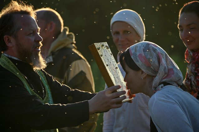 An Orthodox believer kisses an icon during a pilgrimage celebrating the icon of St. Nicholas in the village of Velikoretskoye in Kirov Region, Russia on June 6, 2021. At least 17 thousand pilgrims, loaded with backpacks and some of them barefoot, took part in a five-day and 150-kilometer-long journey from Kirov to the village of Velikoretskoye, according to the local media. (Photo by Alexey Malgavko/Reuters)