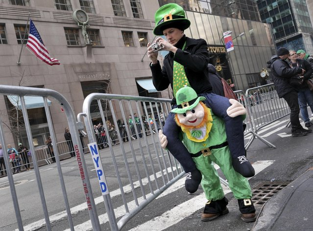 Paul McFadden of Donegal, Ireland, seems to stand on the shoulders of a leprechaun while taking a picture before the start of the St. Patrick's Day Parade in New York, Tuesday, March 17, 2015. (Photo by Seth Wenig/AP Photo)