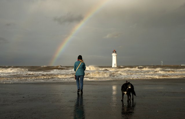 A women walks her dog as a rainbow forms over Perch Rock lighthouse off New Brighton beach, near Wallasey in Britain January 26, 2016. (Photo by Phil Noble/Reuters)