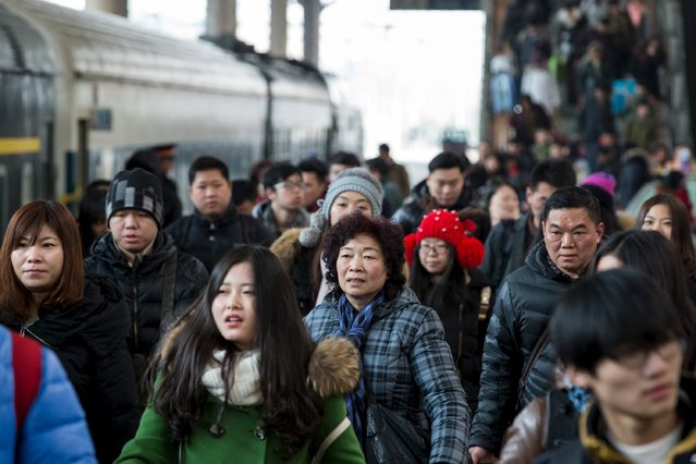 Passengers walk at a railway station, in Nanjing, Jiangsu province, China, January 23, 2016. According to traffic police, over 2.9 billion trips will be made around China during the 40-day Spring Festival travel rush, which started on January 24. (Photo by Reuters/China Daily)