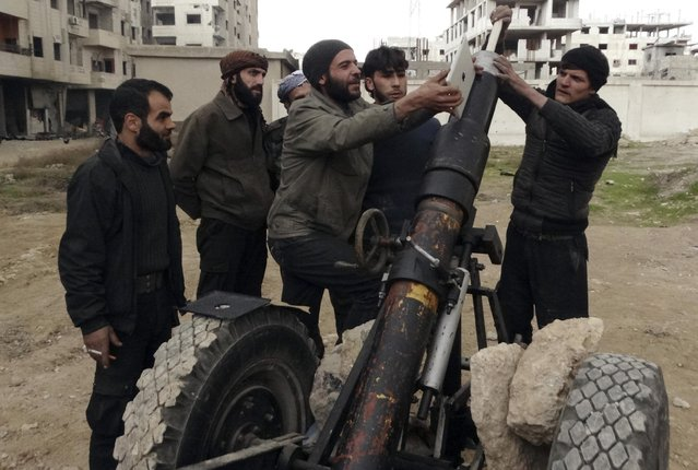 Free Syrian Army fighters use an iPad as they prepare to launch a weapon toward the forces of Syria's President Bashar al-Assad in Ain Tarma, in Eastern Ghouta, a suburb of Damascus January 3, 2015. (Photo by Msallam Abd Albaset/Reuters)