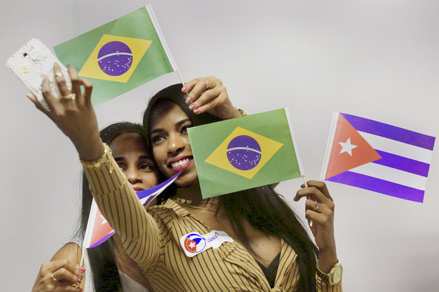 "Cuban doctors holding Brazilian and Cuban flags take a selfie before they and other Cuban physicians return home, at the airport in Brasilia, Brazil, Thursday, November 22, 2018. Cuba announced it is recalling the physicians in the ""More Doctors"" program after Brazilian President-elect Jair Bolsonaro said the program could continue only if doctors get their full pay directly rather from the Cuban government and are able to bring their families with them. (Photo by Eraldo Peres/AP Photo)"