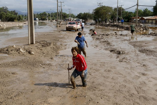 Locals walk through a flooded street at Copiapo city, March 26, 2015. (Photo by Ivan Alvarado/Reuters)