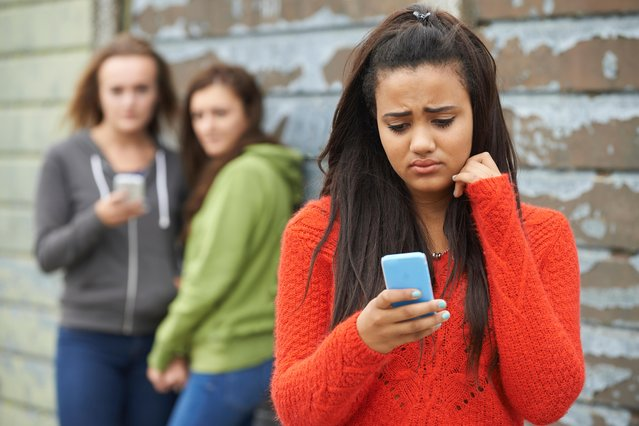 Teenage girl being bullied by text message. (Photo by Highwaystarz-Photography/Alamy Stock Photo)