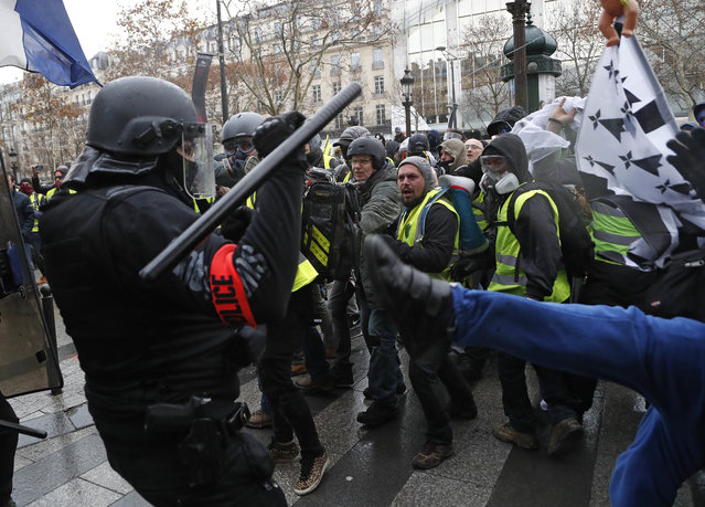 Police officers clash with demonstrators wearing yellow vests in Paris, Saturday, December 8, 2018. (Photo by Thibault Camus/AP Photo)