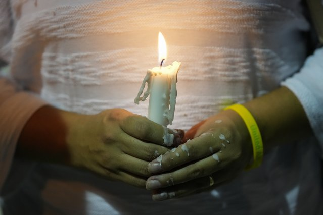 Dislamy Pelayo holds a candle during a multi-faith vigil for victims of the Champlain Towers South condo building collapse, near the site where the building once stood, Thursday, July 15, 2021, in Surfside, Fla. (Photo by Rebecca Blackwell/AP Photo)