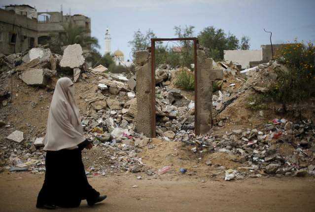 A Palestinian woman walks past the frame of a doorway of a destroyed house, on which British street artist Banksy painted an image of a goddess holding her head in her hand, after the door with the painted image was sold in the northern Gaza Strip, April 1, 2015. (Photo by Mohammed Salem/Reuters)