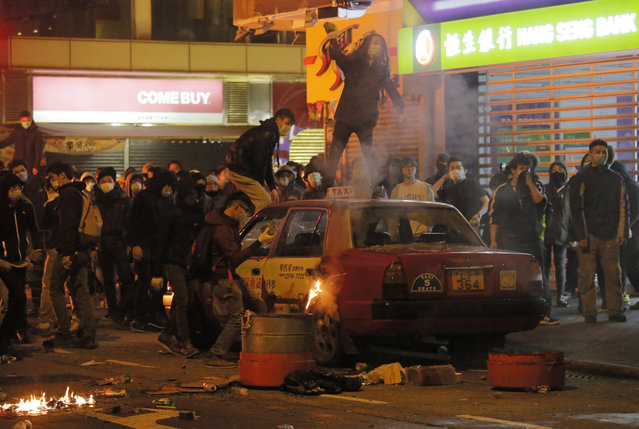 Rioters throw bricks at police in Mong Kok district of Hong Kong, Tuesday, February 9, 2016. (Photo by Vincent Yu/AP Photo)