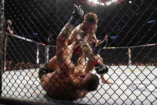 Dustin Poirier, top, punches Conor McGregor during a UFC 264 lightweight mixed martial arts bout Saturday, July 10, 2021, in Las Vegas. (Photo by John Locher/AP Photo)