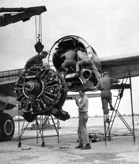 53912 A.C. –  India – Sgt Guy D. Cutter, Detroit, MI, left, and Cpl David Marks, Cincinnati, OH, guide a damaged engine of a Boeing B-29 Superfortress to the ground while three mechanics inspect the engine casing.  (Photo by the National Museum of the USAF)