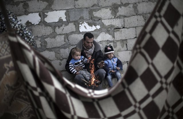 A Palestinian man and his children warm themselves during rainy, cold weather outside their house in a slum on the outskirts of Khan Younis refugee camp, southern Gaza Strip, Wednesday, December 28, 2016. (Photo by Khalil Hamra/AP Photo)