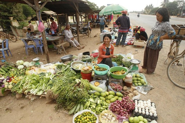 A Cambodian vendor, center, sells her morning vegetable on the sidewalk of main street at a remote rural area of Russey Chroy village, Kandal province, north of Phnom Penh, Tuesday, March 31, 2015. (Photo by Heng Sinith/AP Photo)