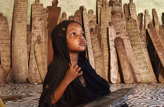 A girl in a madrassa holds a wooden board with verses of the koran written on it in Mogadishu on March 25, 2015. (Photo by Carl De Souza/AFP Photo)