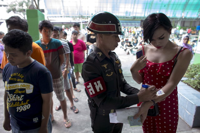 An army officer writes a number on the arm of Thanompong, a 21-year-old transgender, during an army draft held at a school in Klong Toey, the dockside slum area in Bangkok April 5, 2015. (Photo by Athit Perawongmetha/Reuters)
