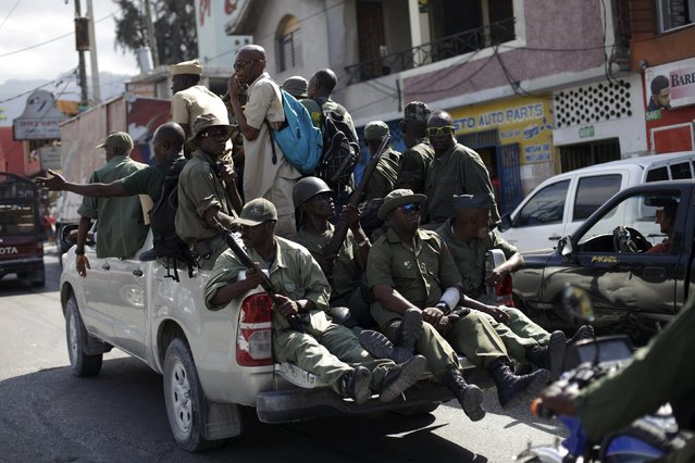 Unidentified men in military style clothes and holding guns drive around Port-au-Prince, Haiti, February 5, 2016. (Photo by Andres Martinez Casares/Reuters)
