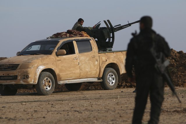 Fighters from the Democratic Forces of Syria position themselves in Ghazila village after taking control of the town from Islamic State forces in the southern countryside of Hasaka, Syria February 17, 2016. (Photo by Rodi Said/Reuters)