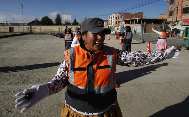 In this November 28, 2013 photo, an Aymara woman cops practices hand-and-arm signals for directing traffic during a training session in El Alto, Bolivia. (Photo by Juan Karita/AP Photo)