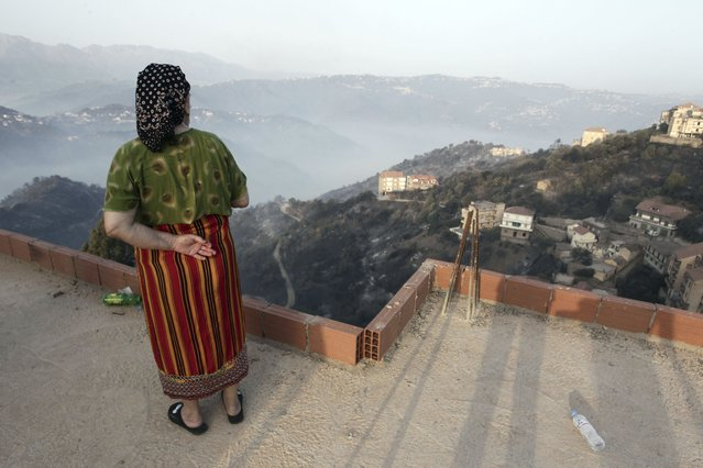A woman looks at the landscape after wildfires in the village of Larbaa Nath Irathen, neat Tizi Ouzou, in the mountainous Kabyle region, 100 kilometers (60 miles) east of Algeria's capital of Algiers, Wednesday, August 11, 2021. At least 25 soldiers died saving residents from wildfires ravaging mountain forests and villages east of Algeria's capital, the president announced Tuesday night as the civilian toll rose to at least 17. (Photo by Fateh Guidoum/AP Photo)
