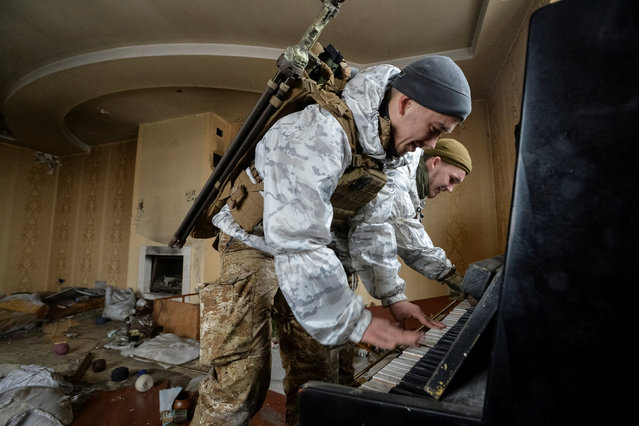 Members of the Ukrainian Armed Forces play the piano in а destroyed house near their position on the front line in Donetsk Region, Ukraine on February 4, 2019. (Photo by Oleksandr Klymenko/Reuters)