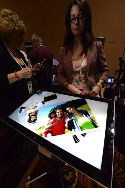 Cassidy Lammers (R) demonstrates the Lenovo Horizon Two touch screen computer during the Unveiled press preview event for the 2014 International Consumer Electronics Show (CES) at the Mandalay Bay Convention Center in Las Vegas, Nevada, USA, 06 January 2014. (Photo by Michael Nelson/EPA)