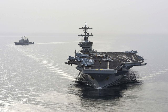The aircraft carrier USS Theodore Roosevelt (CVN 71) and the guided-missile cruiser USS Normandy (CG) 60 sail in the Arabian Sea, in this U.S. Navy photo taken April 16, 2015. The ships will join seven other U.S. warships in the waters near Yemen, which is torn by civil strife as Iranian-backed Houthi rebels battle forces loyal to the U.S.-backed president. (Photo by Mass Communication Specialist Seaman Anna Van Nuys/Reuters/U.S. Navy)