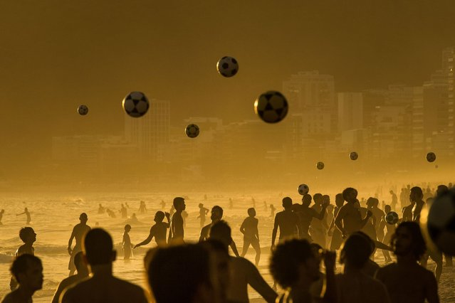 People play football at sunset at Ipanema Beach in Rio de Janeiro, Brazil, on January 14, 2014. (Photo by Yasuyoshi Chiba/AFP Photo)