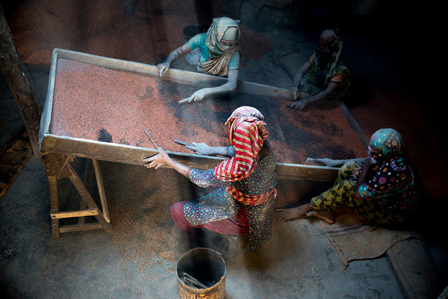 """""""Women workers"""". Bangladesh. """"I took this photo inside a workhouse where women were working under a tin roof. The beam of sunlight came from a broken shade"""". (Photo by Abm Jahidul Islam)"""