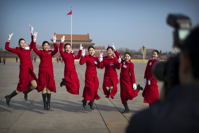 Bus ushers leap as they pose for a group photo during a meeting one day ahead of the opening session of China's National People's Congress (NPC) at the Great Hall of the People in Beijing, Monday, March 4, 2019. (Photo by Mark Schiefelbein/AP Photo)