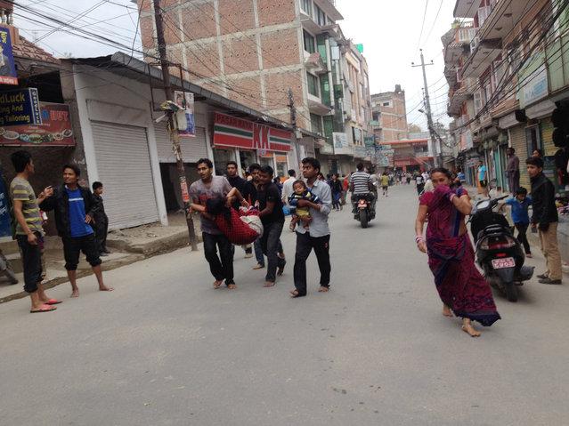 In this photo provided by Guna Raj Luitel, an injured woman is carried just after an earthquake in Kathmandu, Nepal, Saturday, April 25, 2015. (Photo by Guna Raj Luitel/AP Photo)