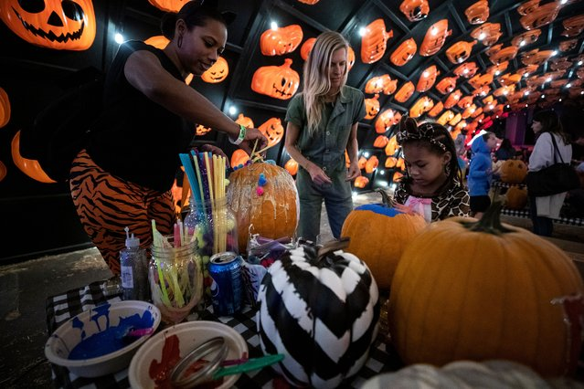 """Jianna, four years old, paints a pumpkin during the open-air Halloween event """"Haunt O'ween"""" in Woodland Hills, Los Angeles, California, USA, 30 September 2021. The event runs from 01 to 31 October 2021. (Photo by Etienne Laurent/EPA/EFE)"""