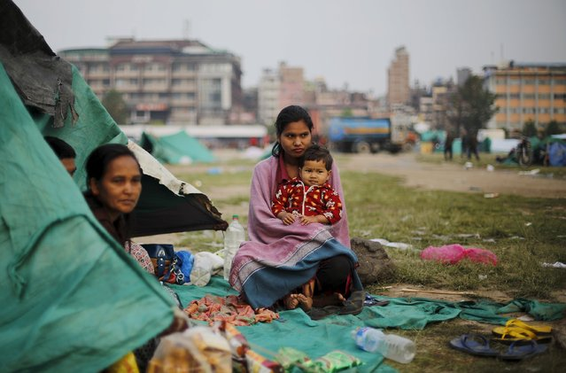 An earthquake victim holds her daughter as she sits outside her makeshift shelter on open ground in the early hours in Kathmandu, Nepal April 28, 2015. (Photo by Adnan Abidi/Reuters)
