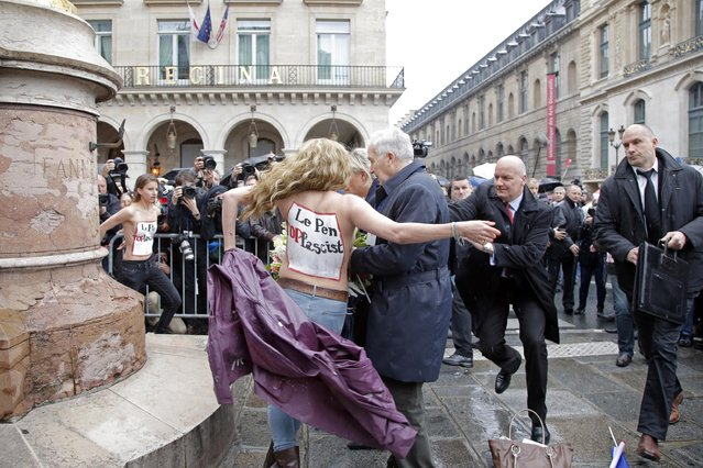 FEMEN activists with Le Pen Top Fascist painted on their bodies appear as France's far-right National Front president Marine Le Pen places a wreath at Joan of Arc Statue during its annual May Day march, in Paris, France, Friday, May 1, 2015. France's far-right National Front is holding its annual May Day march, but for the first time the party's founder Jean-Marie Le Pen – on the outs with his daughter who presides over the party – is not taking a seat at the tribune. (Photo by Francois Mori/AP Photo)