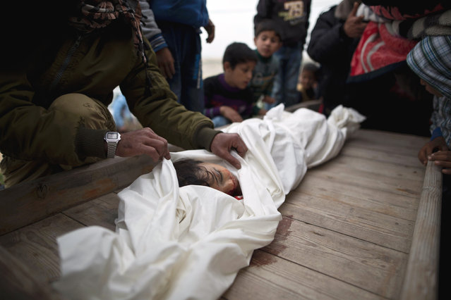 Palestinians mourn over the body of Israa Abu Khussa, 6, during her funeral on March 12, 2016 in Beit Lahiya in the north of the Gaza strip. A six-year-old girl wounded in an Israeli air strike on the Gaza Strip on March 12 has died of her injuries, Palestinian medical sources told AFP, naming her as Israa Abu Khussa. Her brother Yassin, 10, died earlier in a raid on a base of Hamas's military wing near their home in the northern Gaza village of Beit Lahiya. Another brother, Ayub, 13, suffered moderate injuries. (Photo by Mahmud Hams/AFP Photo)
