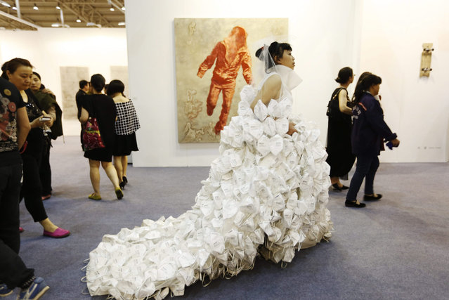 "Chinese artist Kong Ming walks in a wedding dress she created made up of 999 face masks titled ""Marry the Blue Sky"" during a VIP preview of the Art Beijing Art Fair, in Beijing, China, 30 April 2015. About 140 art galleries and art organizations participated in the tenth year of the annual art fair, which runs from 01 to 03 May. (Photo by How Hwee Young/EPA)"