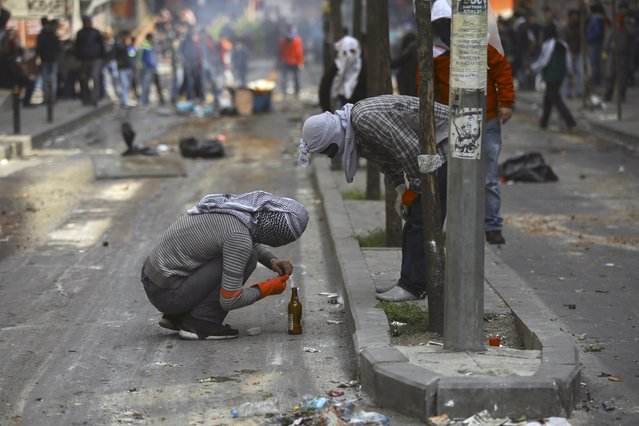 Two protesters prepare Molotov cocktails during clashes with police in Okmeydani neighborhood in Istanbul, Turkey, May 1, 2015. Turkish police fired tear gas and water cannon at hundreds of stone-throwing May Day protesters on Friday, after they defied a ban and tried to march on Istanbul's Taksim Square. (Photo by Huseyin Aldemir/Reuters)
