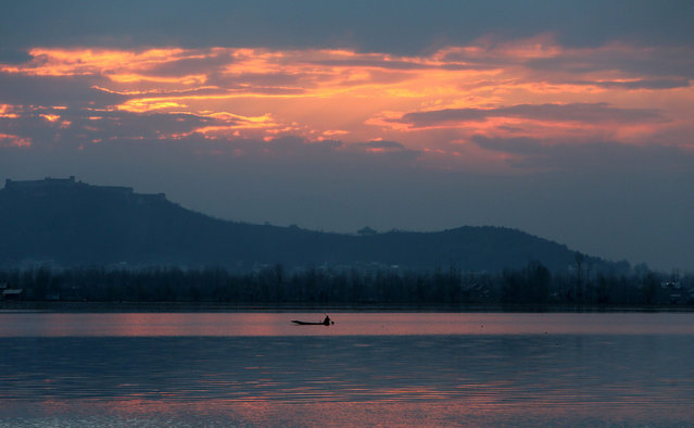 A Kashmir boatman rows a boat at sunset in world famous Dal Lake in Srinagar, the capital of Indian Kashmir, 20 March 2015. Weather was bright and sunny in Srinagar after a week of bad weather conditions. (Photo by Farooq Khan/EPA)