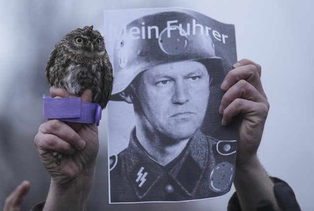 A pro-government protester holds up a baby owl and an image of Romanian President Klaus Iohannis depicted as a Nazi soldier of Hitler's paramilitary SS Schutzstaffel organisation in front of the presidential office in Bucharest, Romania, February 6, 2017. (Photo by Octav Ganea/Reuters/Inquam Photos)