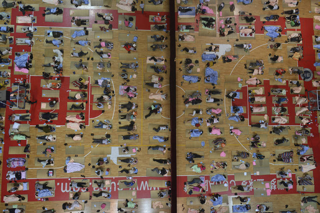 Parents of freshmen students sleep on mats laid out on the floor of a gymnasium at Huazhong Normal University in Wuhan, Hubei province, China, September 7, 2013. (Photo by Reuters/China Daily)