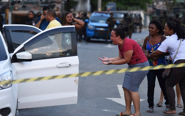 A woman cries out in agony as she looks at the body of Evaldo dos Santos Rosa slumped inside his car in the Guadalupe neighborhood of Rio de Janeiro, Brazil, Sunday, April 7, 2019. Authorities say soldiers mistook Evaldo dos Santos Rosa's for that of criminals and was hit by 80 shots fired by members of the armed forces, killing him and wounding his wife's stepfather. His wife, 7-year-old son and another woman were unharmed, according to relatives. (Photo by Fabio Teixeira/AP Photos)