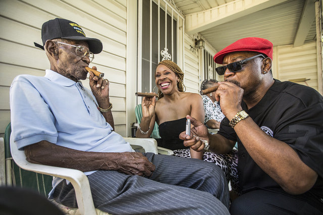 Richard Overton, left,  smokes a cigar with a few neighborhood friends Donna Shorts, center and Martin Wilford Sunday, May 3, 2015, in Austin, Texas. Overton, is considered to be the oldest living World War II veteran in the United States, celebrated his 109th birthday on a front porch in East Austin with friends and family. Wilford, right, says that he has known Overton for 37 years and he looks at Mr. Overton as if he was his biological father.  (Photo by Ricardo B. Brazziell/AP Photo/Austin American-Statesman)