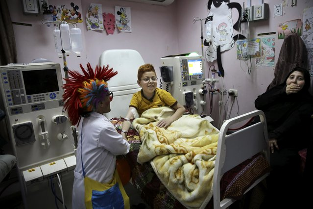 """In this Thursday, March 17, 2016 photo, Palestinian clown doctor Alaa Miqdad, left, entertains 13-year-old Mohammed Al-Qunfod who suffers from dialysis, in the department of kidney diseases at Al-Rantisi children's hospital in Gaza City. Miqdad and his partner visit three medical centers in the Gaza Strip a week and spend two days at Al-Rantisi, a specialized hospital for children with chronic illnesses. """"As much as we can, we try to let the child respond to us to reach his heart; his insides"""". (Photo by Adel Hana/AP Photo)"""