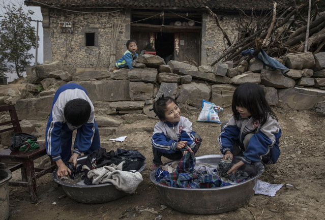 """""""Left behind"""" child Luo Hongniu, 8 (C) washes clothes with brother Luo Gan, 10, and sister Luo Hongni, 11, right, outside the family house on December 18, 2016 in Anshun, China. (Photo by Kevin Frayer/Getty Images)"""