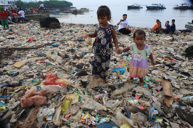 Children walk on garbage as others take part in an event to clear garbage from Lampung bay in the Sukaraja village in the Bumi Waras subdistrict of Bandar Lampung on February 21, 2019. Officials from the local government, residents and the police took part in the annual event. (Photo by Perdiansyah/AFP Photo)