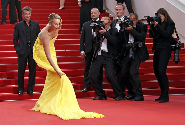 "Cast member Charlize Theron adjusts her dress as actor Sean Penn looks on as they pose on the red carpet during arrivals for the screening of the film ""Mad Max: Fury Road"" out of competition at the 68th Cannes Film Festival in Cannes, southern France, May 14, 2015. (Photo by Eric Gaillard/Reuters)"