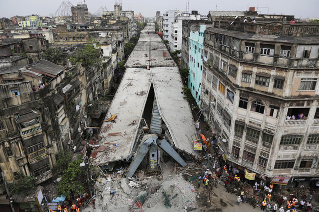 General view shows a partially collapsed overpass in Kolkata, India, Friday, April 1, 2016. The overpass spanned nearly the width of the street and was designed to ease traffic through the densely crowded Bara Bazaar neighborhood in the capital of the east Indian state of West Bengal. About 100 meters (300 feet) of the overpass fell, while other sections remained standing. (Photo by Bikas Das/AP Photo)