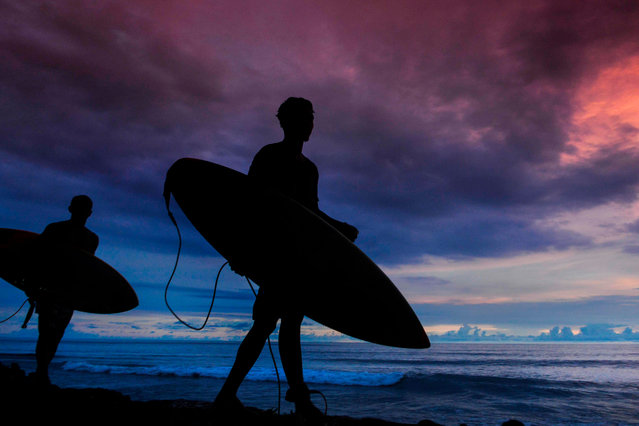 Indonesian men walk with their surf boards at sunset in Tapaktuan beach, Southern Aceh province on April 14, 2019. (Photo by Chaideer Mahyuddin/AFP Photo)