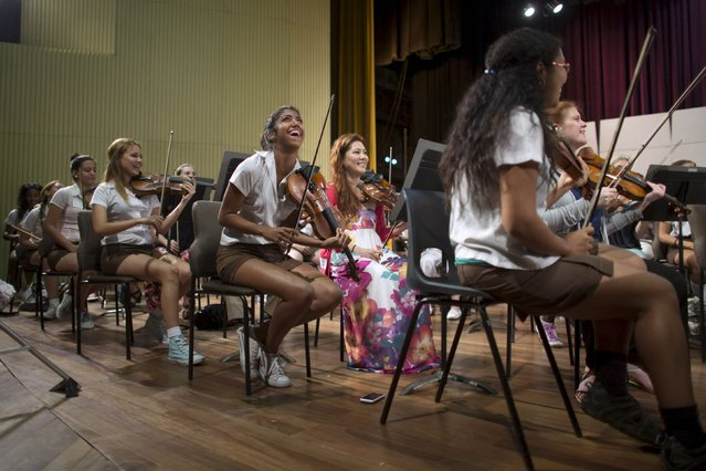 Music student Daniele Gonzalez, (centre row, L), and Australian musician Susie Park from the Minnesota Orchestra (centre row, 2nd L), react during a rehearsal in Havana, May 15, 2015. (Photo by Alexandre Meneghini/Reuters)