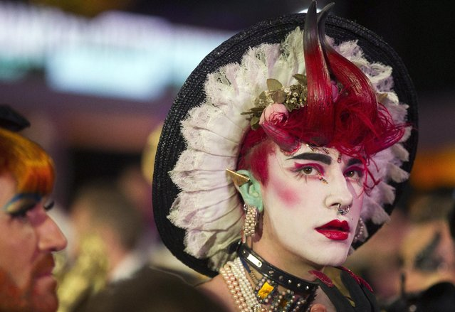 A costumed guest poses for photographers during the opening ceremony of the Life Ball in front of City Hall in Vienna, Austria, Saturday, May 16, 2015. (Photo by Herwig Prammer/AP Photo)