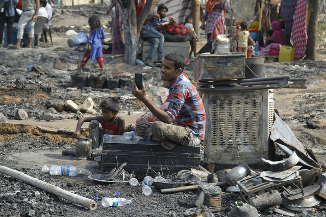 A man makes a video call to his relatives sitting amidst his belongings he salvaged after a fire at a slum area  on the outskirts of Jammu, India, Monday, June 3, 2019. More than 150 huts of a shantytown were gutted down in a major fire that broke out late on Sunday night. The cause of fire is yet to known and there were no human causalities, police said on Monday. (Photo by Channi Anand/AP Photo)